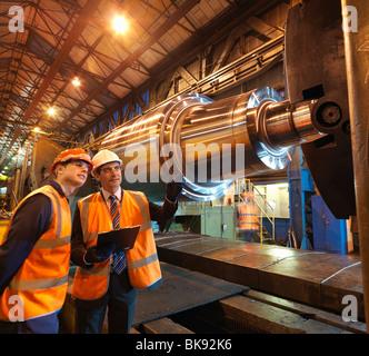 Engineer & Apprentice With Steel Roller - Stock Photo