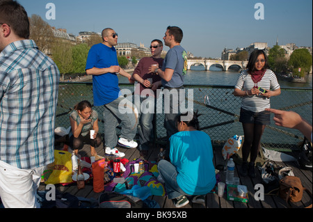 Paris, France, Group Tourist and French Teenagers Picnicking on Pont des Arts Bridge on Seine River - Stock Photo