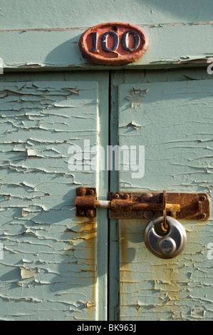 A beach hut, number 100, on Hove Esplanade, with its rusty bolt and padlock. - Stock Photo