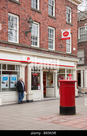 Street scene outside a Post Office with postbox with people. Warrington, Cheshire, England, UK. - Stock Photo