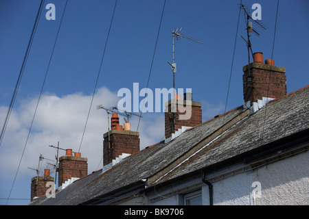row of red bricked chimney pots on terraced house rooves with tv aerials and overhead telephone wires in the uk - Stock Photo