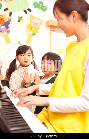 Nursery Teacher Playing Piano with Children - Stock Photo