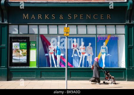 Woman in Veil pushing Pushchair past Swimwear Window Display York UK - Stock Photo