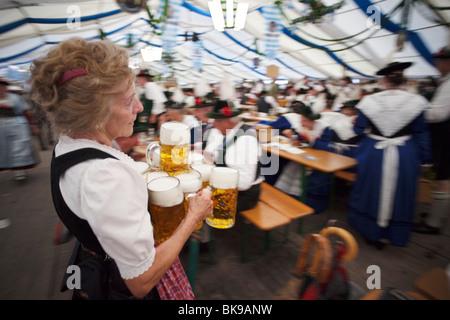 Senior waitress with beer steins during Oktoberfest, Munich, Bavaria, Germany - Stock Photo