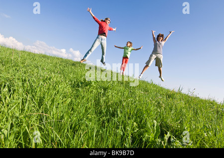 Family playing on a grassy hill, Italy. - Stock Photo