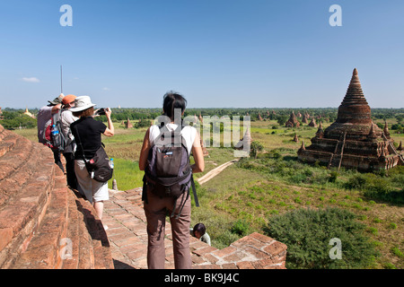 Tourist contemplating the view from the top of a temple. Buledi group temples. Bagan. Myanmar - Stock Photo