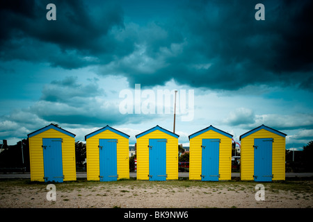 Yellow and Blue beach huts under a moody sky on Littlehampton beach, West Sussex - Stock Photo