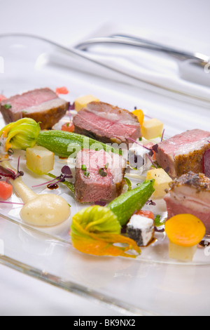 Lamb served with vegetables and sauce - Stock Photo
