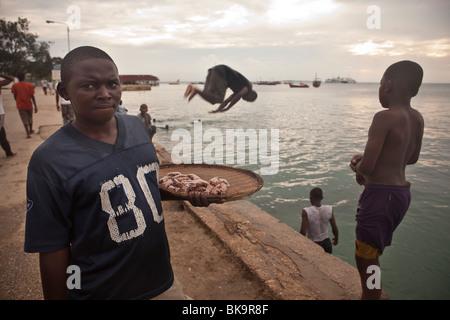 Boys swimming in the harbour - Stonetown, Zanzibar, Tanzania. - Stock Photo