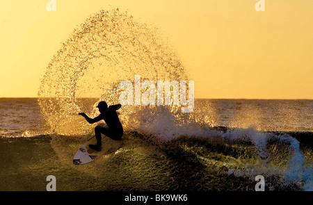 A surfer is silhouetted by the sun at Brims Ness, near Thurso, Scotland. The sun sets in the north of Scotland. - Stock Photo