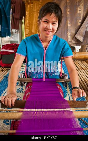 Young woman weaving cloth on loom; Patara Elephant Farm, Chiang Mai Province, Thailand. - Stock Photo