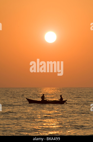 Two people in a boat in the sea at sunset - Stock Photo