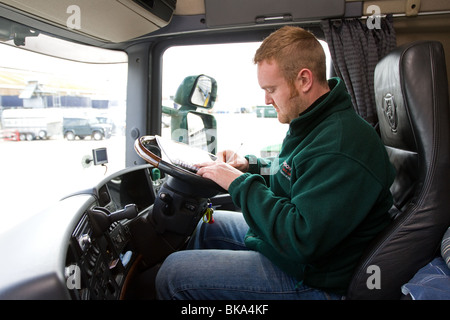 A Lorry driver changing a tachograph card in his cab - Stock Photo