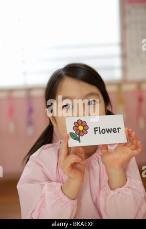Kindergarten Girl Holding Picture Card - Stock Photo