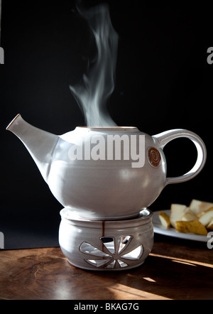 Steaming teapot with freshly brewed tea - Stock Photo