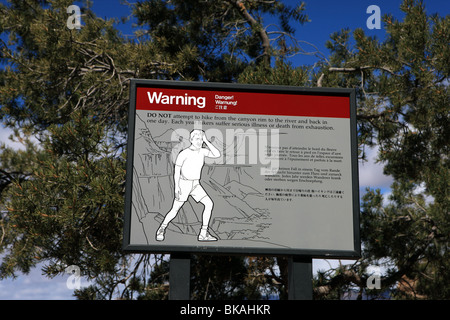 Warning sign for hikers in the Grand Canyon National Park stating the dangers of walking in this area - Stock Photo