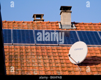 French solar panel / panels and satellite / TV dish on the roof of a farm house in Alpine / Alps region of Savoy, - Stock Photo