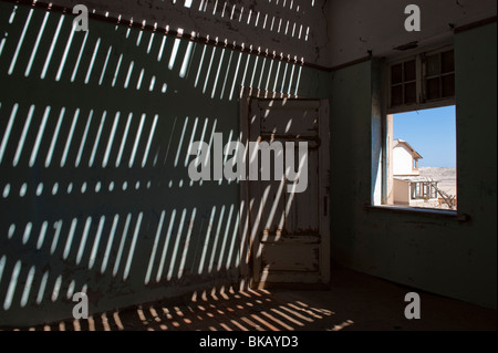 Light Penetrates through the old floorboards casting shadows on the walls, Buchhalter House in Kolmanskop near Luderitz, - Stock Photo