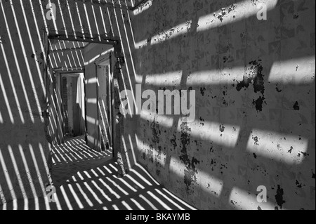 Light Penetrates through the old floorboards casting shadows on the walls, Engineers House in Kolmanskop near Luderitz, - Stock Photo