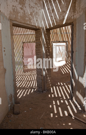 Light Penetrates through the old floorboards casting shadows and interesting patterns in the Engineers House, Kolmanskop - Stock Photo
