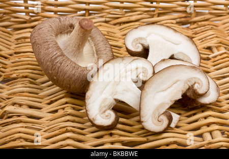 Whole and sliced raw Shiitake Mushrooms against wicker basket. - Stock Photo