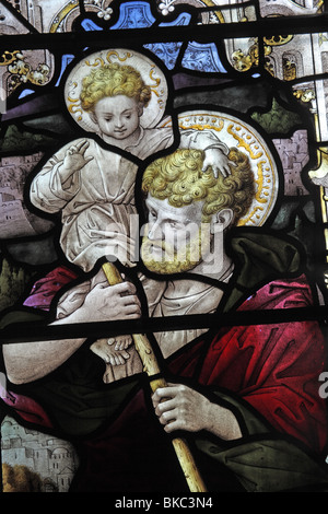 A stained glass window depicting St Christopher carrying the infant Jesus across the stream - Stock Photo