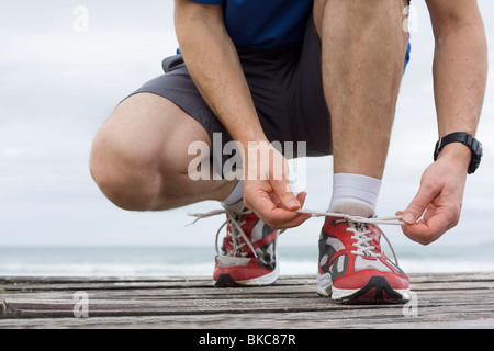 Runner tying shoelace in front of the sea - Stock Photo