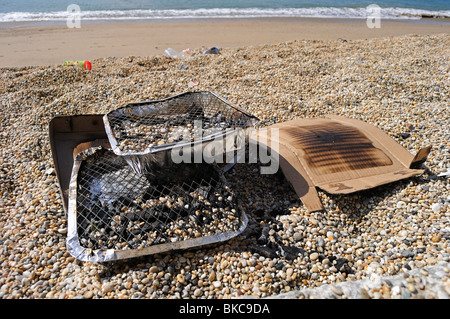 old barbeque trays left on the beach at porthleven in cornwall, uk - Stock Photo