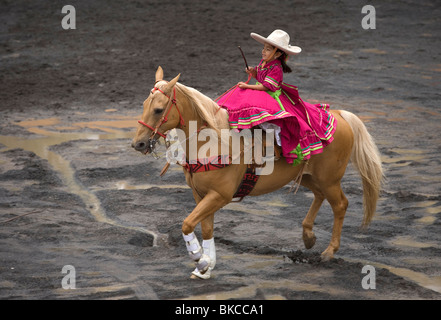 A five-years-old amazona girl from the Metropolitan escaramuza team rides her horse in Mexico City - Stock Photo