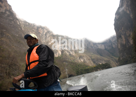 A tour guide steers a boat in the Grijalva River in the Sumidero Canyon in Tuxla Gutierrez, Chiapas, Mexico, February - Stock Photo