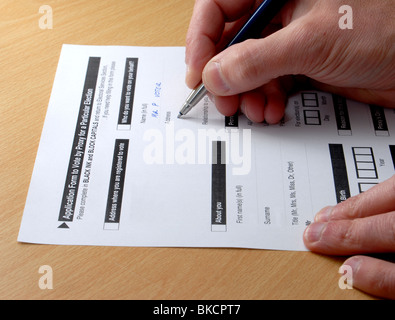 Completing an application form to apply for proxy or postal vote for an upcoming election - Stock Photo