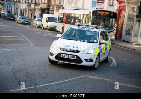 Police car speeding through a city street in England. - Stock Photo