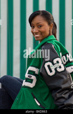 A young adult African American female is sitting, smiling and wearing a high school letter jacket (Class of '03) - Stock Photo