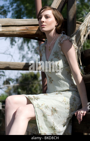 A beautiful young Caucasian woman sits on some old wooden stairs looking off into the distance. - Stock Photo