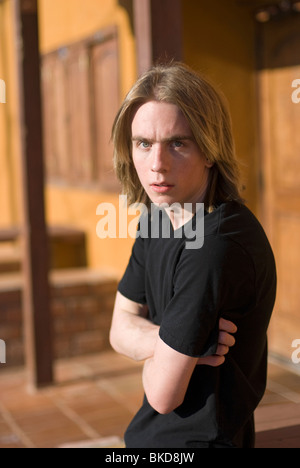 An 18-20 year old man wearing a black t-shirt, looks tough with his arms folded (vertical) - Stock Photo