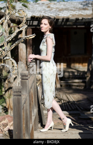 A beautiful young Caucasian woman stands among some wood remains of an old house.  She is wearing a pastel green - Stock Photo