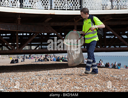 Council workman picking up litter on beach Brighton England UK - Stock Photo