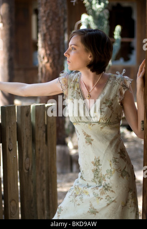 A beautiful young Caucasian woman stands near a gate wearing a pastel green dress. - Stock Photo