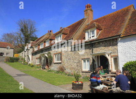 Customers at The Tiger Inn enjoy a drink on the village green at East Dean, East Sussex. - Stock Photo