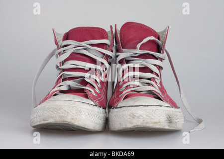 A pair of worn, red Chuck Taylor Converse All Star casual boots. - Stock Photo