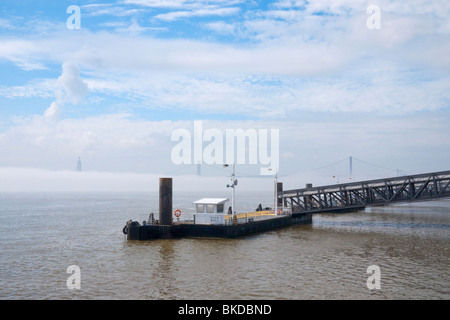 View of River Tagus, Statue of Christ (Cristo Rei) and 25 de Abril Bridge (1966) shrouded in mist, Lisbon, Portugal. - Stock Photo