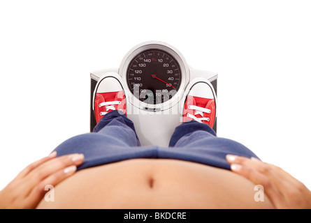 Athletic young girl measuring her weight on a balance - Stock Photo