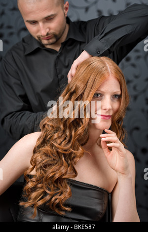 Professional hairdresser with long red curly hair fashion model at luxury salon - Stock Photo