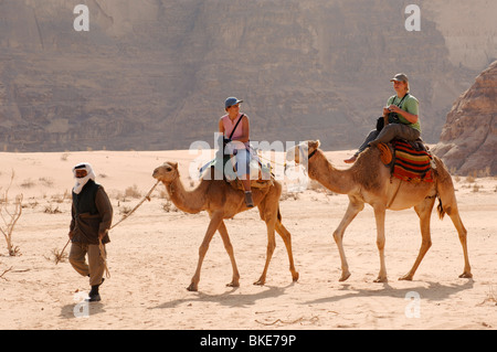 Bedouin guide and visitors on camels, Wadi Rum Protected Area, Jordan - Stock Photo