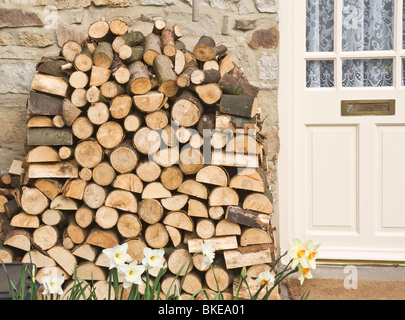 firewood stacked outside a cottage door in the Yorkshire Dales. - Stock Photo