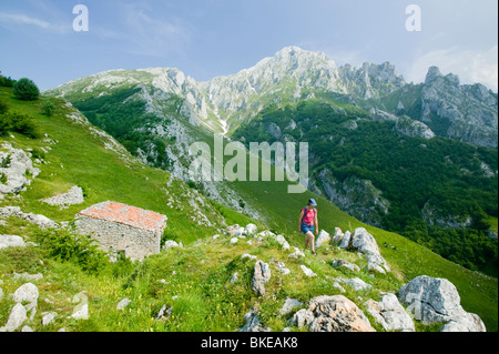A woman walking above the mountain village of Sotres in the Picos de Europa National Park northern Spain - Stock Photo