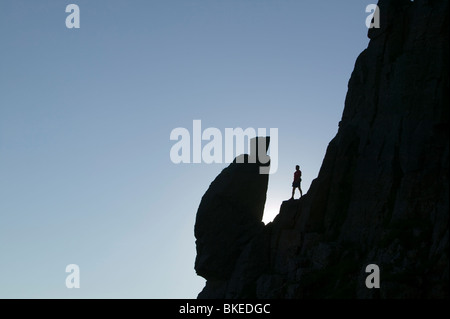 A climber silhouetted by the Spinx rock on Great Gable in the Lake District UK - Stock Photo