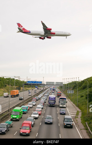 traffic congestion on the M1 motorway at Loughborough with a plane coming into land at East Midlands Airport - Stock Photo