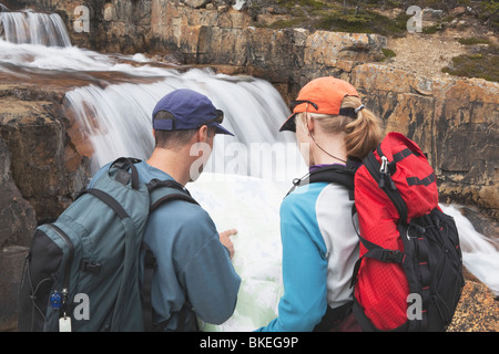 Lake Louise, Alberta, Canada; A Couple Hiking And Looking At A Map Next To The Waterfall At Giant Steps - Stock Photo