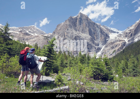 Yoho National Park, British Columbia, Canada; A Couple Hiking Through The Mountains And Looking At A Map - Stock Photo
